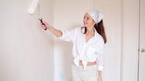 De jonge vrouw schildert de ruimte in het witte kleur en glimlachen stock video