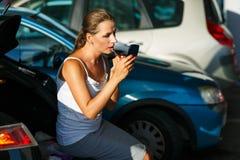 De jonge vrouw schildert haar lippen zittend op de boomstam van een auto op Royalty-vrije Stock Foto's