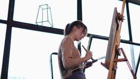 De jonge vrouw schildert olievervenachtergrond op canvas, dat zich op een schildersezel bevindt stock footage