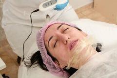 De jonge vrouw in schoonheidssalon doet ultrasone klankschil en gezichts het reinigen procedure stock fotografie