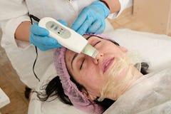 De jonge vrouw in schoonheidssalon doet ultrasone klankschil en gezichts het reinigen procedure royalty-vrije stock afbeelding