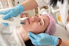 De jonge vrouw in schoonheidssalon doet ultrasone klankschil en gezichts het reinigen procedure stock foto's