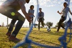 De jonge vrouw schopt voetbal terwijl het spelen met vrienden stock afbeeldingen
