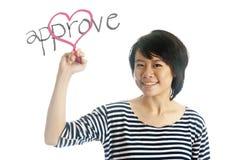 De jonge vrouw schrijft goedkeurt haar hart Royalty-vrije Stock Afbeelding