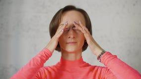 De jonge vrouw sluit haar ogen met vingers op lichte achtergrond stock footage
