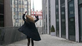 De jonge vrouw spint merrily op de straat stock video