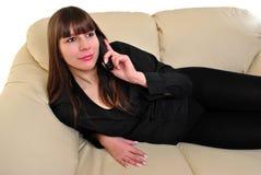 De jonge vrouw spreekt op een telefoon stock fotografie