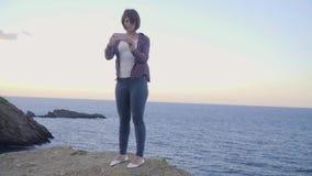 De jonge vrouw status bovenop een berg neemt beeldenoverzees Zonsondergang stock videobeelden