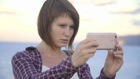 De jonge vrouw status bovenop een berg neemt beeldenoverzees Zonsondergang stock video