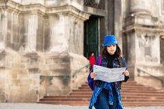 De jonge vrouw status dichtbij de kerk in oude stad Lviv, en houdt een kaart in hand ukraine stock foto