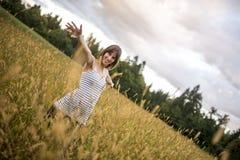 De jonge vrouw status in het midden van de herfstweide met hoogte gaat Royalty-vrije Stock Afbeeldingen