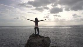 De jonge vrouw status op rots, kijkt aan oceaan en heft handen op stock video