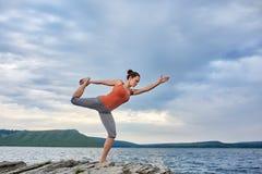 De jonge vrouw status in yoga stelt op de grote steen dichtbij mooie rivier Royalty-vrije Stock Afbeelding
