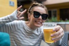 De jonge vrouw steunt bier in een plastic kop De nadruk op bier, defocused opzettelijk vrouw Het concept voor dronken, partij, vi stock fotografie