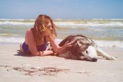 De jonge vrouw streelt haar hond bij strand stock afbeeldingen