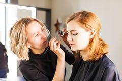 De jonge vrouw in de studio maakt een professionele samenstelling stock fotografie