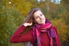 De jonge vrouw in sweater en sjaal met lang haar stelt voor portra stock afbeelding