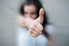 De jonge vrouw toont duim Stock Fotografie