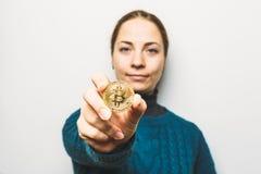De jonge vrouw toont Gouden Bitcoin-muntstuk - symbool van cryptocurrency, nieuw virtueel geld, selectieve nadruk Royalty-vrije Stock Foto