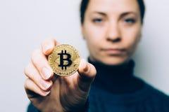 De jonge vrouw toont Gouden Bitcoin-muntstuk - symbool van cryptocurrency, nieuw virtueel geld, selectieve nadruk Royalty-vrije Stock Afbeeldingen