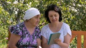De jonge vrouw toont haar bejaarde moeder hoe te om de tablet te gebruiken stock footage