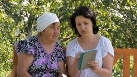 De jonge vrouw toont haar bejaarde moeder hoe te om de tablet te gebruiken stock video