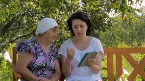 De jonge vrouw toont haar bejaarde moeder hoe te om de tablet te gebruiken stock videobeelden