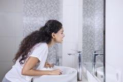 De jonge vrouw toont haar tanden in de spiegel royalty-vrije stock foto's