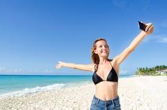 De jonge vrouw toont het strand Stock Foto's