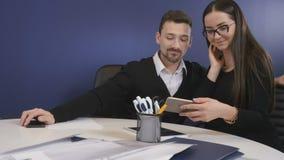 De jonge vrouw toont iets op haar smartphone aan de man stock videobeelden