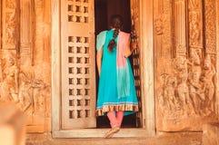 De jonge vrouw in traditionele Sari opent de deur van Hindoese tempel met de hulp van de steenmuur, India Gesneden architectuur v Stock Afbeeldingen