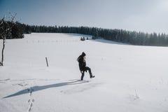 De jonge vrouw treft grote maatregelen in de diepe die sneeuw van een gebied in sneeuw wordt behandeld stock afbeeldingen