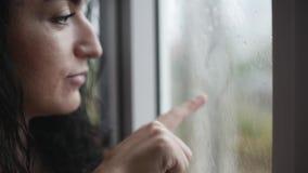 De jonge vrouw trekt een hart op a misted venster, glimlachend, buiten het venster op de straat het het regenen van ` s stock video