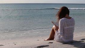 De jonge vrouw van achter zitting door het overzees bekijkt de horizon bij dageraad in de wind, gekleed in een wit kantkleding en stock footage