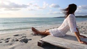 De jonge vrouw van achter zitting door het overzees bekijkt de horizon bij dageraad in de wind, gekleed in een wit kantkleding en stock videobeelden