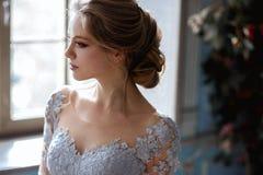 De jonge vrouw van de blondebruid in een lichtblauwe huwelijkskleding Royalty-vrije Stock Foto's