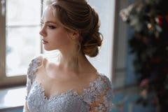 De jonge vrouw van de blondebruid in een lichtblauwe huwelijkskleding Stock Afbeelding