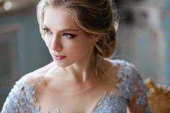 De jonge vrouw van de blondebruid in een lichtblauwe huwelijkskleding Stock Fotografie
