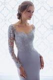 De jonge vrouw van de blondebruid in een lichtblauwe huwelijkskleding Stock Foto's