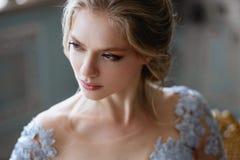 De jonge vrouw van de blondebruid in een lichtblauwe huwelijkskleding Stock Afbeeldingen