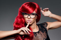 De in jonge vrouw van de luxemanier met rood gekruld haar in glas Stock Afbeelding