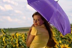 De jonge vrouw van de schoonheid met paraplu in zonnebloemen Stock Foto's