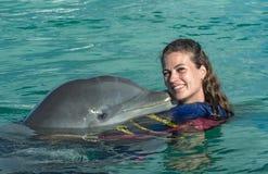De jonge vrouw van de dolfijnkus in blauw water Glimlachende vrouw die met dolfijn zwemmen De blauwe Abstracte Achtergrond van he stock afbeelding