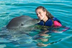 De jonge vrouw van de dolfijnkus in blauw water Glimlachende vrouw die met dolfijn zwemmen De blauwe Abstracte Achtergrond van he royalty-vrije stock foto
