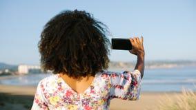 De jonge vrouw van het Afrokapsel bij het strand die foto nemen stock foto