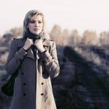 De jonge vrouw van het manierblonde in beige laag en het grijze sjaal lopen openlucht royalty-vrije stock fotografie