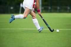 De jonge vrouw van de hockeyspeler met bal in spel van het aanvals het speelhockey stock foto's