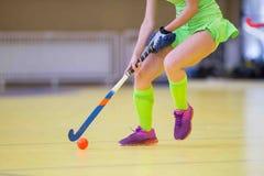 De jonge vrouw van de hockeyspeler met bal in spel van het aanvals het speelhockey stock afbeelding