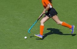 De jonge vrouw van de hockeyspeler met bal in spel van het aanvals het speelhockey royalty-vrije stock foto's