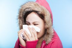 De jonge Vrouw vangt een koude en het niezen neus met een sweater isola Stock Foto